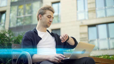 Young man with laptop on legs sitting on a bench, consulting his watch. Outdoors blond man in casual clothes looking at the watch on background of blurred house