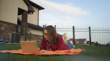 Young girl with laptop lying on the lawn at the backyard of the house, working outdoors. Young woman in eyeglasses with earphones and laptop on background of private house
