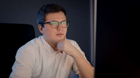 Closeup of man in white shirt and eyeglasses in front of the computer. Businessman occupied working late in night in home office