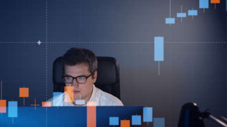 Businessman analyzing a graphic of a motion stock exchange chart. A young handsome trader looking at a stock diagram on the big screen of the computer Stock fotó