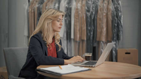Young female manager with laptop on background of coats on hangers in design studio. Young female making notes sitting to table in design studio