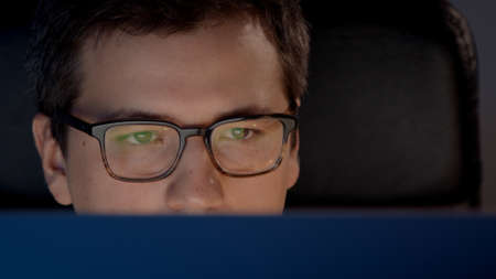 Closeup of man eyes in eyeglasses in front of the computer in home office, concentrated look. Young man sitting at home working alone at night