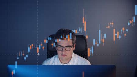 Businessman analyzing a graphic of a motion stock exchange chart. A young handsome trader looking at a stock diagram on the big screen of the computer