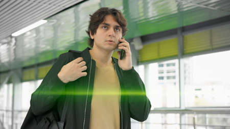Young man talking on the phone, walking at the airport indoors. Glass windows on background, caucasian man in black jacket and backpack, hand luggage middle shot