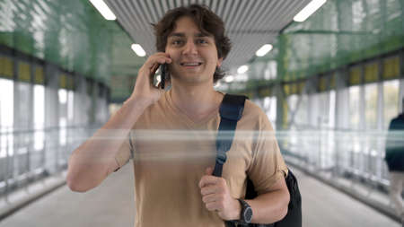 Young man talking on the phone, walking at the airport indoors. On background of lamps and glass windows, caucasian man in beige shirt with bag and phone in hand Stock fotó
