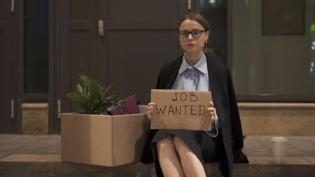 Young woman in eyeglasses office clothes with a sign job wanted sitting with cardboard box and cup of coffee. Woman in office skirt looking for a job on the street, looking at the camera