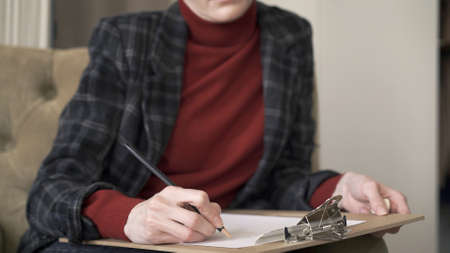 Female manager no face, sitting in chair, middle shot, making notes looking at the papers on lap. Woman in red sweater and jacket wearing working in a soft chair Stock fotó
