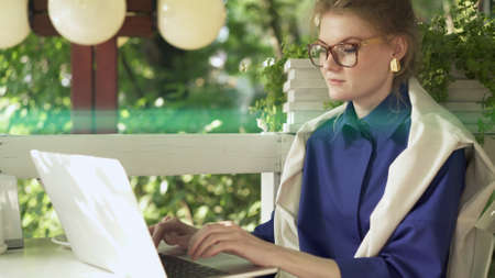 Woman in big eyeglasses enjoying free time at cafe table outdoors, checking social networks. On background of green trees, lens flare