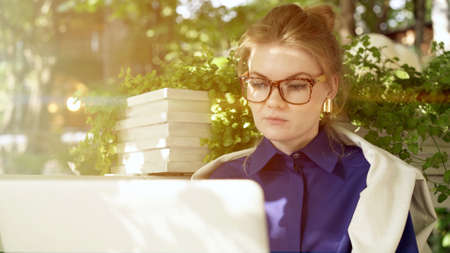 Young woman in big eyeglasses and blue shirt close up sitting at cafe terrace, checking social networks. On background of green plants, lens flare Stock fotó
