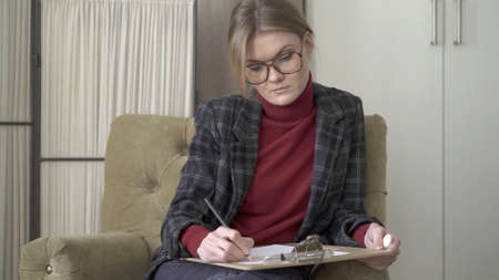 Female manager in eyeglasses sitting in chair, middle shot, making notes looking at the papers on lap. Woman in red sweater and jacket wearing big eyeglasses working in a soft chair
