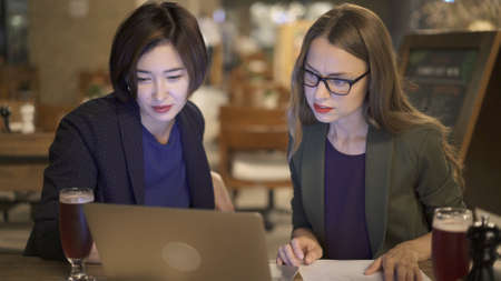 Two women friends sitting at the bar with laptop, blond woman in eyeglasses on background of empty chairs. Two women discussing in an open space bar Stock fotó