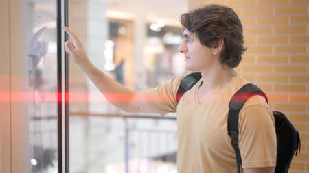 Man in beige shirt standing using information panel, navigation in mall. Side view of young guy tapping on a big board searching for information in a city mall, blurred background Stock fotó