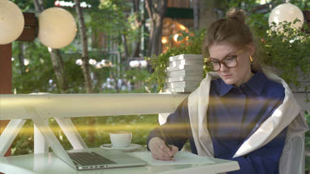 Young woman student in big eyeglasses and blue shirt making notes at cafe table outdoors, with laptop on table. On background of green trees, lens flare