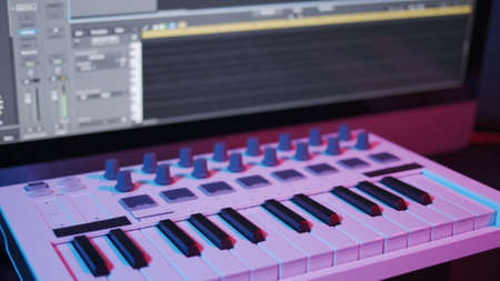 Male hands recording music, playing electronic keyboard, midi keys on the table with neon lights. Closeup of male hands composing music in night, music sequencer and midi controller