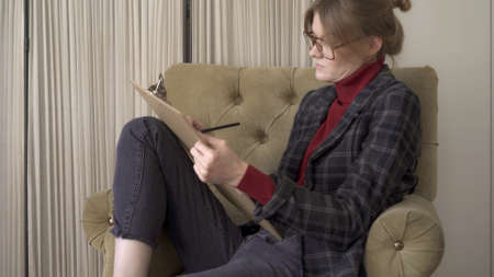 Manager in eyeglasses with legs in the chair, making notes looking at the papers. Woman in red sweater and jacket wearing big eyeglasses working in a soft chair