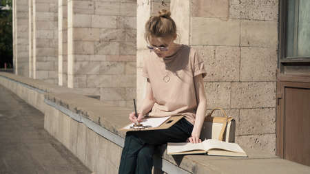 Young woman learning outside near university building, alone young student in sunglasses writing out information from the book. Summer sunny day, preparing for the exam Stock fotó