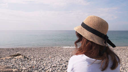 Young woman in hat enjoying horizon, water and sky. Back of woman in white blouse and wicker hat on background of pebbles, water and cloudy sky in a resort town
