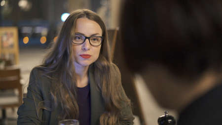 Young woman in eyeglasses with a cup of red beer sitting to table with her friend. Two women discussing in an open space bar, back of a brunette woman