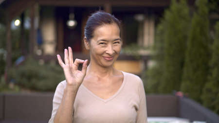 Asian woman smiling showing ok sign near private house, looking at the camera, blurred background. Adult woman owner of a modern private country house backyard