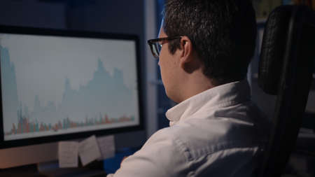 Home trader analysing trading charts on stock market on computer screen at home. Over the shoulder shot of man in eyeglasses looking at the screen with stock graphs