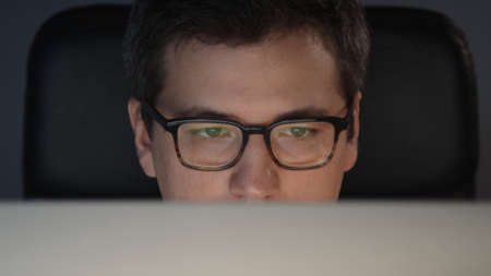 Closeup of man eyes in eyeglasses in front of the computer in home office on background of grey wall. Young man sitting at home working alone at night Stock fotó