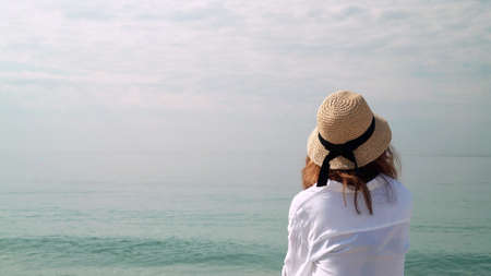 Young woman in hat enjoying horizon, water and sky. Back of woman in white blouse and wicker hat on background of water, ocean and cloudy sky