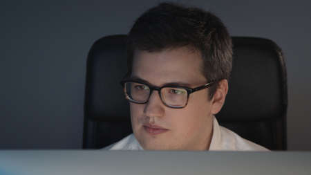 Closeup of man in eyeglasses in front of the computer in home office on background of grey wall. Young man sitting at home working alone at night Stock fotó