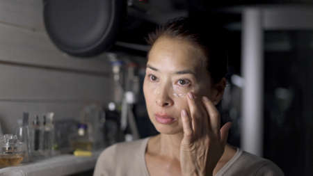 Asian woman putting concealer on face portrait shot, close up. Asian adult woman doing make up indoors, in the bathroom, using cosmetics