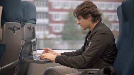 Young guy with laptop sitting in train, student in black jacket studying while traveling. Young man concentrated typing in a train, working while traveling