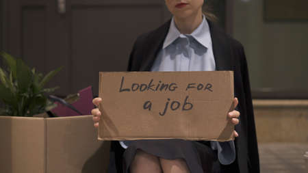 Young woman in office clothes with a sign looking for a job sitting with cardboard box. Woman in office skirt looking for a job on the street, no face