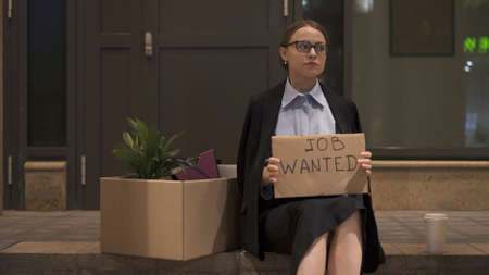 Young woman in eyeglasses office clothes with a sign job wanted sitting with cardboard box and cup of coffee. Woman in office skirt looking for a job on the street