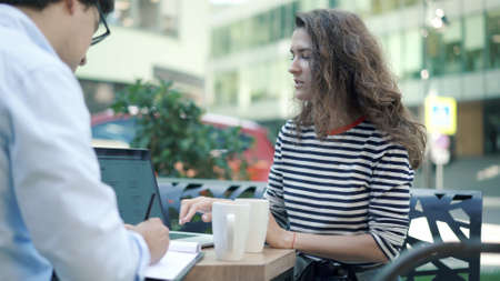 Woman drinking coffee and looking at the laptop, concentrated young woman and man discussing work progress at the cafe outdoors on background of city road