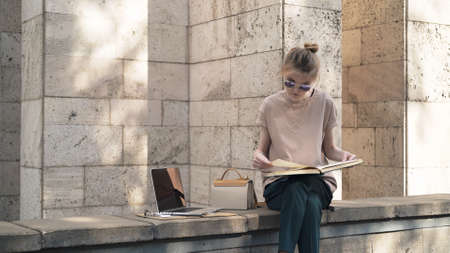 Young woman learning outside with laptop book in hand near university building, alone young student in sunglasses studying outdoors. Summer sunny day, preparing for the exam Stock fotó