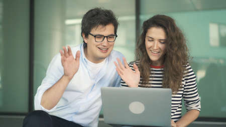 Young man and woman with laptop chatting gesturing in a video conference. Two young students with laptop on background of glass office buildings Stock fotó