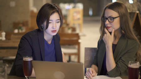 Two women friends sitting at the bar with laptop, blonde woman in eyeglasses with an asian woman. Two women discussing in an open space bar