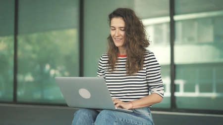 Smiling woman with laptop working on background of glass windows, blurred background. Middle shot of female with curly hair and striped sweater looking at the laptop, chatting