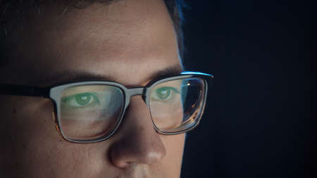 Closeup of man eyes in eyeglasses in front of the computer, close up, concentrated look. Young man sitting working alone at night