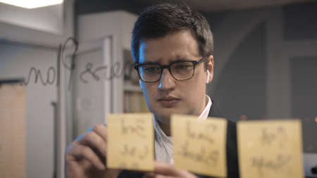 Young businessman in suit writing plans on the transparent glass wall in the office. Front view of man in earbuds and eyeglasses writing plans on glass in the office room