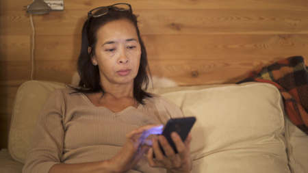 Asian woman scrolling the phone, serious look, reading news. Middle shot of woman with eyeglasses on head, sitting on a sofa with phone in hand, yellow light