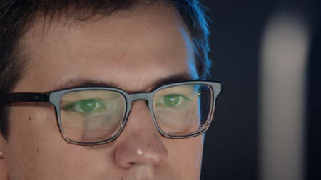 Closeup of man eyes in eyeglasses in front of the computer, gimbal pan shot right to left, concentrated look. Young man sitting working alone at night