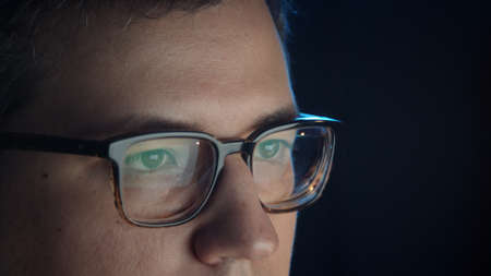 Closeup of man eyes in eyeglasses in front of the computer, concentrated look. Young man sitting working alone at night