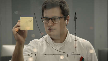 Young businessman writing graphs on the transparent glass wall in the office. Front view of man with earbuds in eyeglasses writing on sticky notes, drawing graphs on glass in the office room