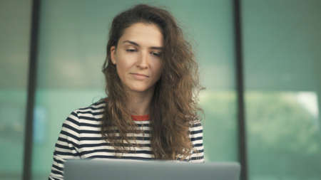 Woman with laptop working on background of glass buildings, blurred background. Portrait shot of female with curly hair and striped sweater looking at the laptop