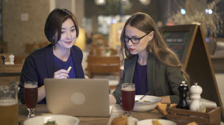 Two women friends sitting at the bar eating with laptop, blond woman in eyeglasses sitting on background of empty chairs. Two women smiling discussing in an open space bar