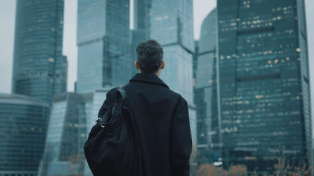 Rear view of a young unrecognizable businessman walking slowly and looking at skyscrapers in a summer evening. Moscow city background.