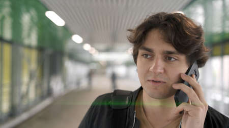 Young man talking on the phone, the airport background lights indoors. Glass windows on background, man close up with phone in hand, airport taxi