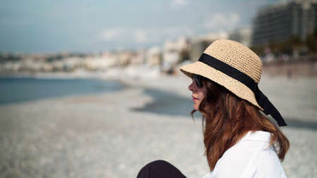 Young woman in hat sitting by the beach in the resort town. Woman closeup in white blouse sitting by the water, looking at sea and dreaming on background of blurred beach and city buildings Stock fotó