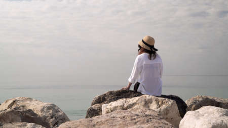 Young woman in hat sitting on a big stones on background of water and cloudy sky. Woman in white blouse sitting by the water, looking at sea and dreaming
