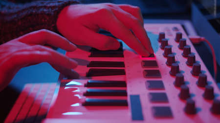 Closeup of hands composing music in night using midi controller. Playing beat music with electronic keyboard, midi keys on the table with neon lights Stock fotó