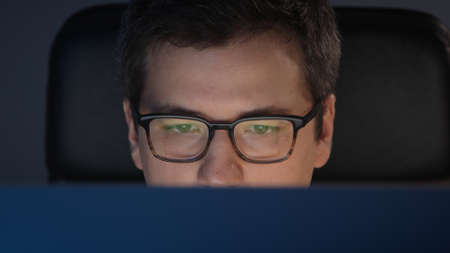 Closeup of man eyes in eyeglasses in front of the computer, pan shot left to right in home office, concentrated look. Young man sitting at home working alone at night